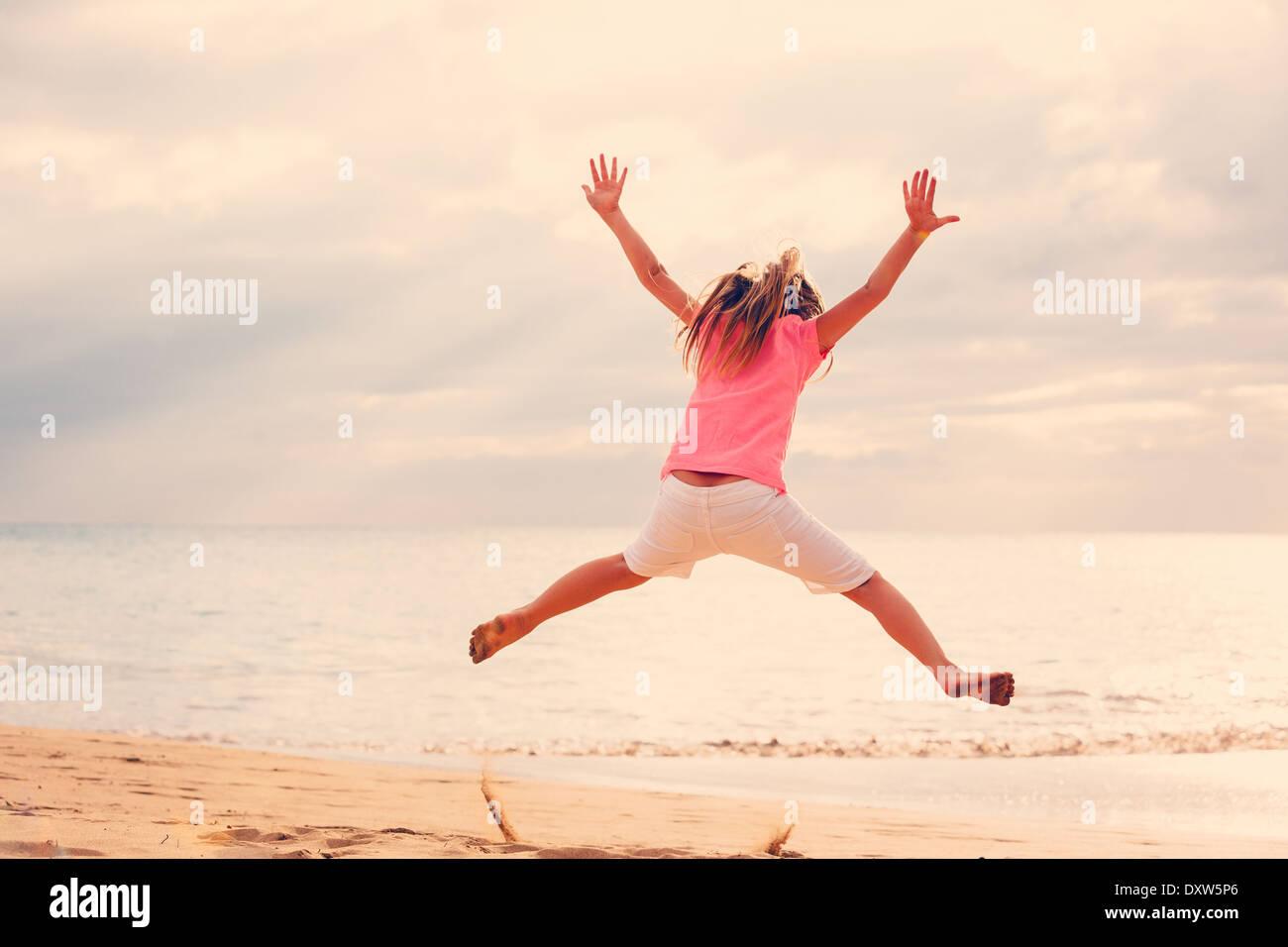 Heureuse Jeune fille sautant de joie sur la plage au coucher du soleil Photo Stock