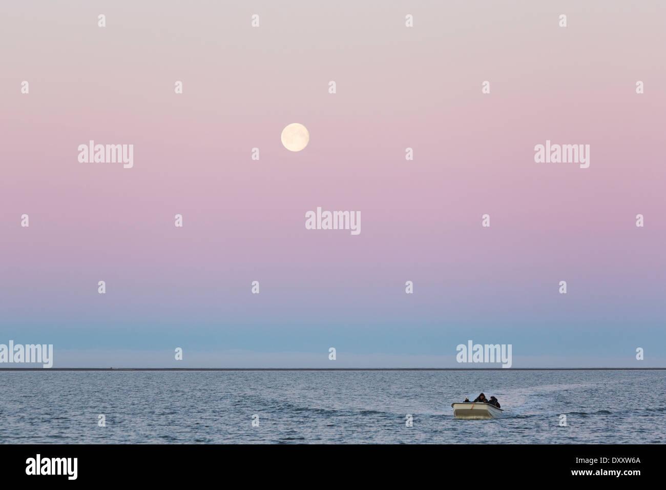 Retour en bateau sur les côtes de l'île Barter en vertu d'un soir de pleine lune, l'Alaska arctique Photo Stock