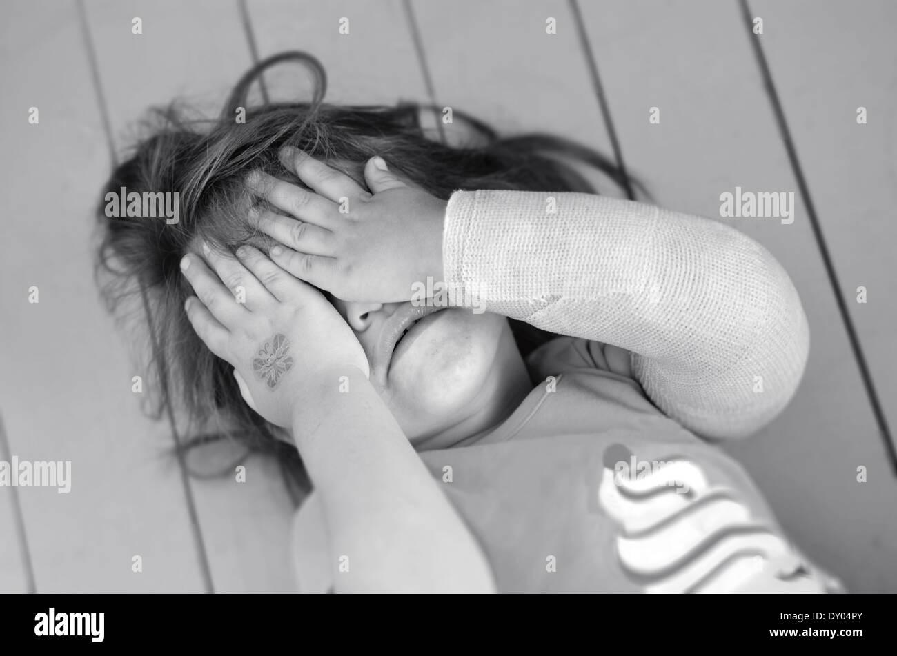 Abusé de petite fille avec un bras cassé couvrant ici visage tout en pleurant. Photo concept de violence Photo Stock
