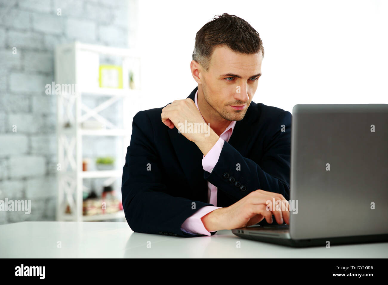 Confident businessman working on a laptop at office Photo Stock