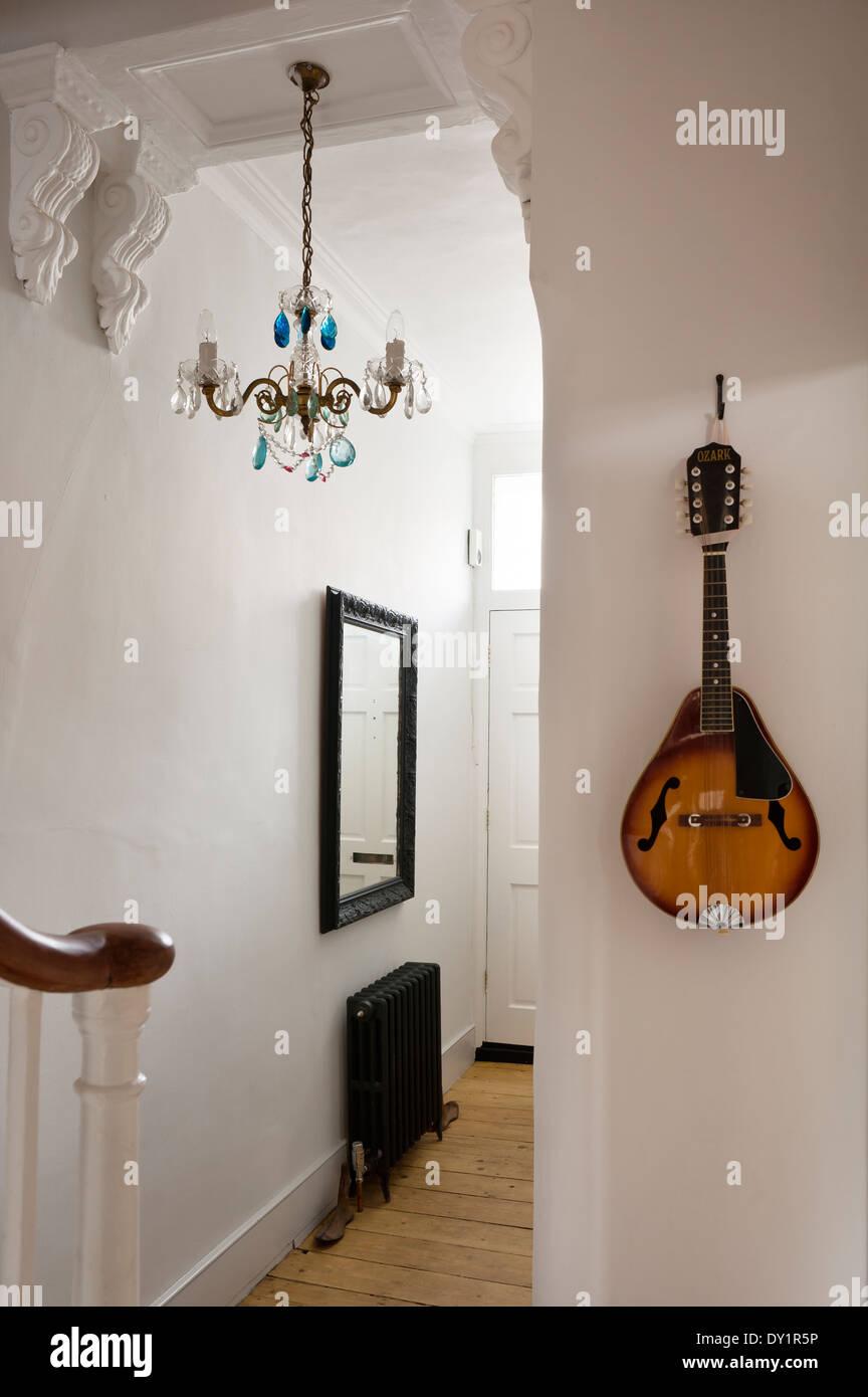 Une mandoline est suspendu sur le mur d'un hall d'entrée avec modillons et lustre bleu bleu Photo Stock