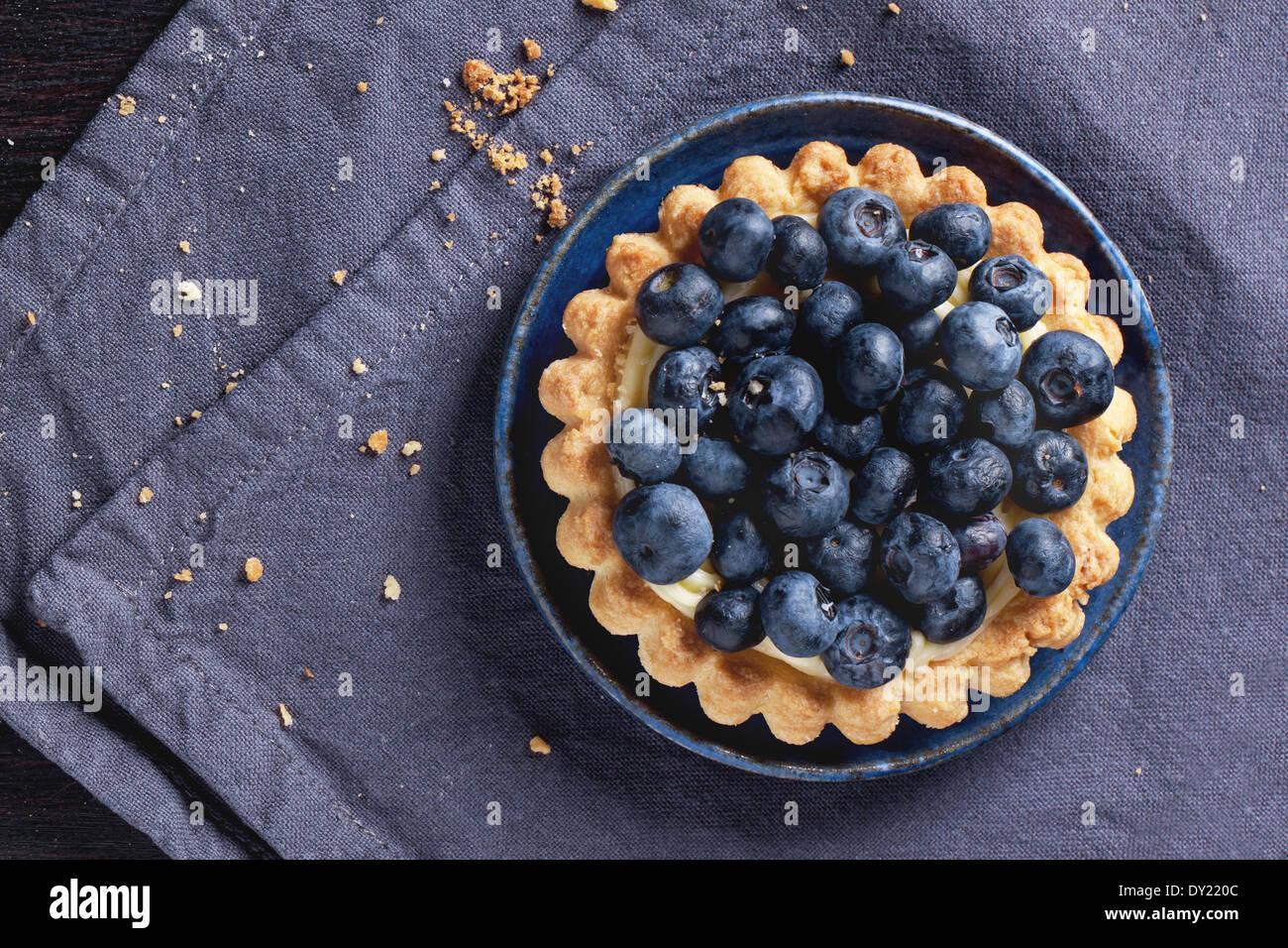 Vue de dessus sur tarte aux bleuets servis sur une plaque en céramique bleu sur serviette textile. Photo Stock