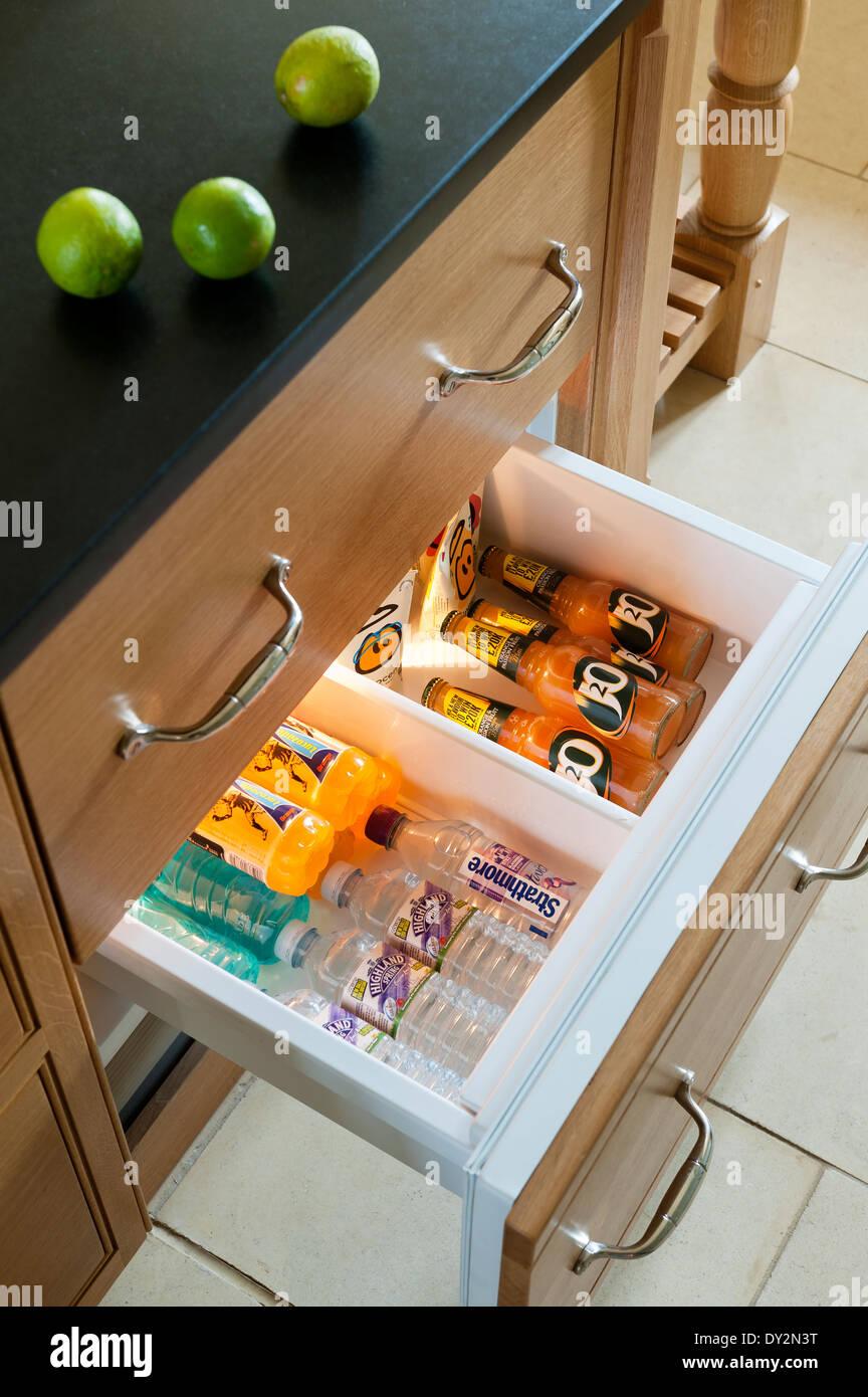 L'eau en bouteille et des jus de fruits dans le réfrigérateur tiroir Photo Stock