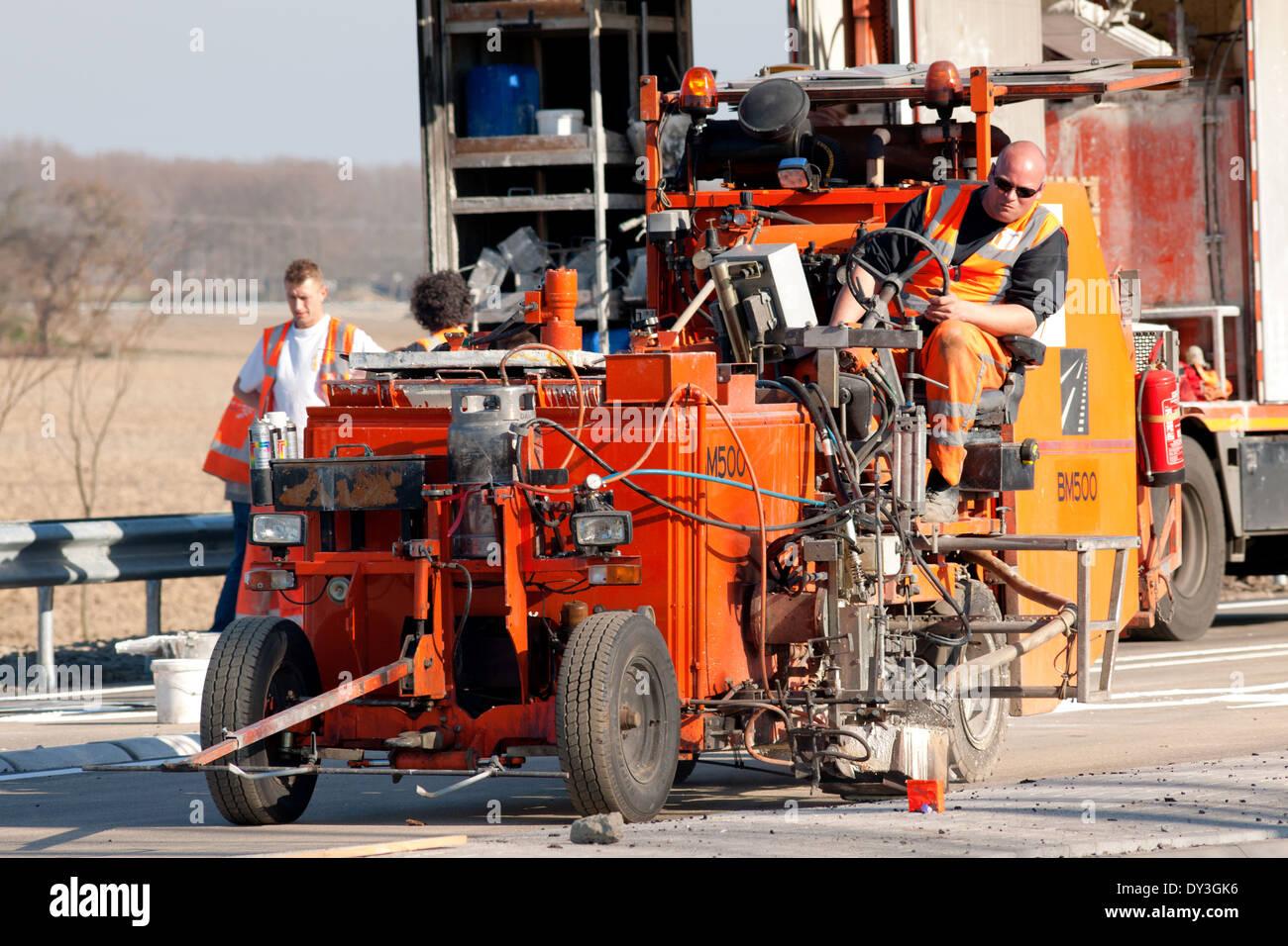Les travailleurs de la route avec un pulvérisateur le marquage routier Photo Stock