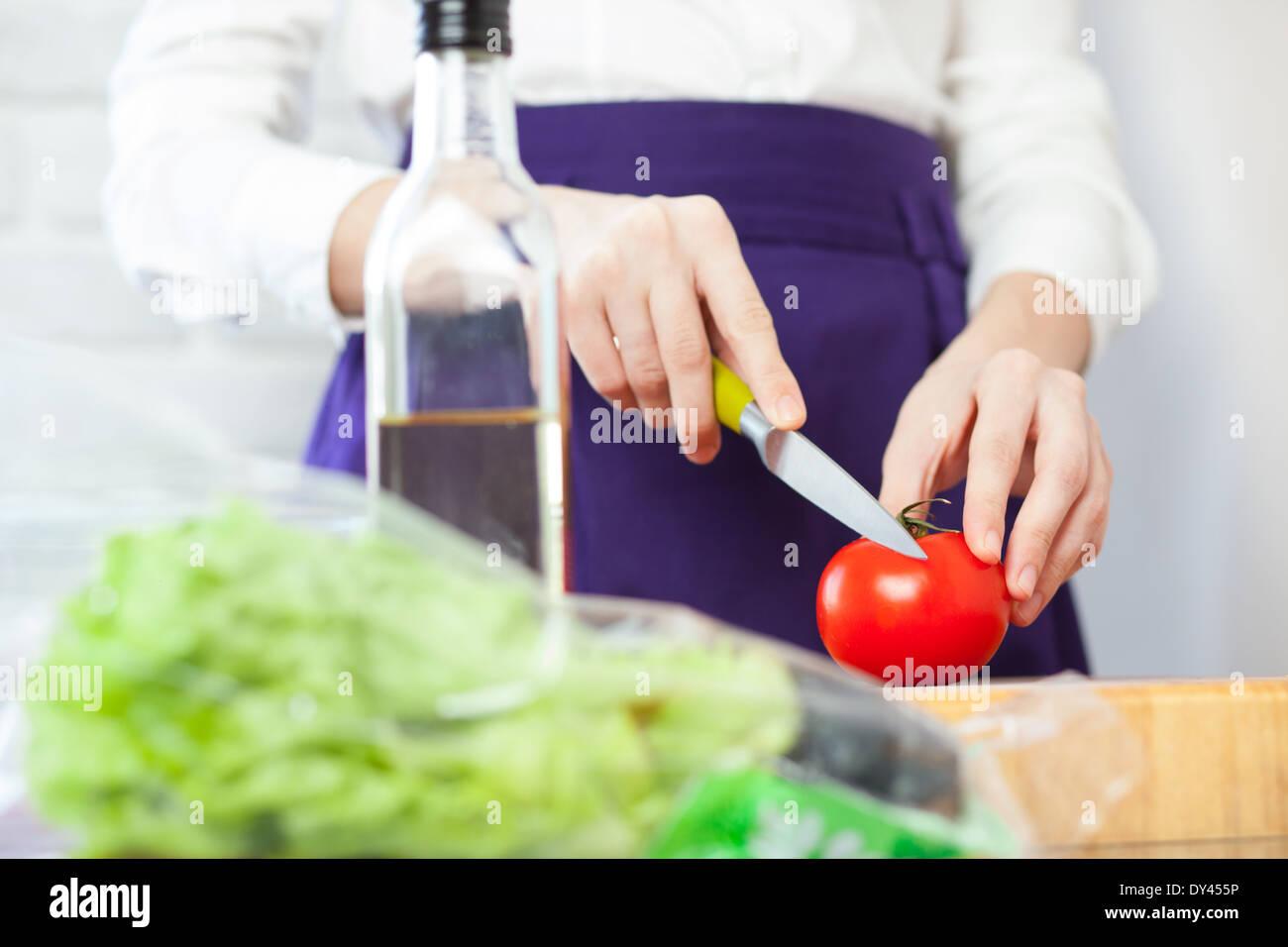 La coupe d'un chef féminin pour la salade de tomates Photo Stock