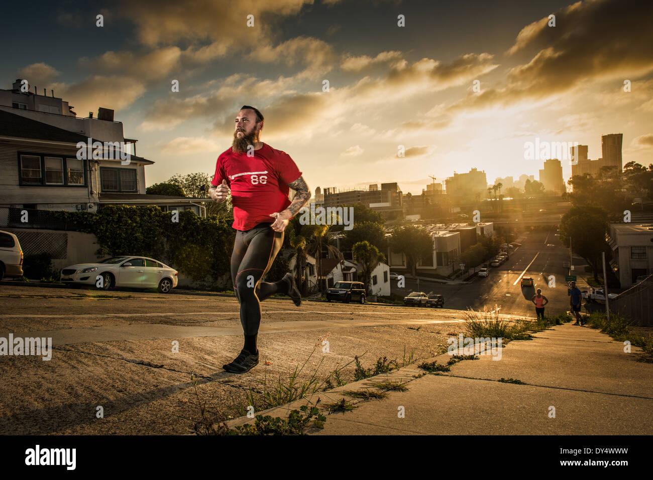 Mid adult male runner et coéquipiers courir vers le haut d'une colline escarpée ville Photo Stock