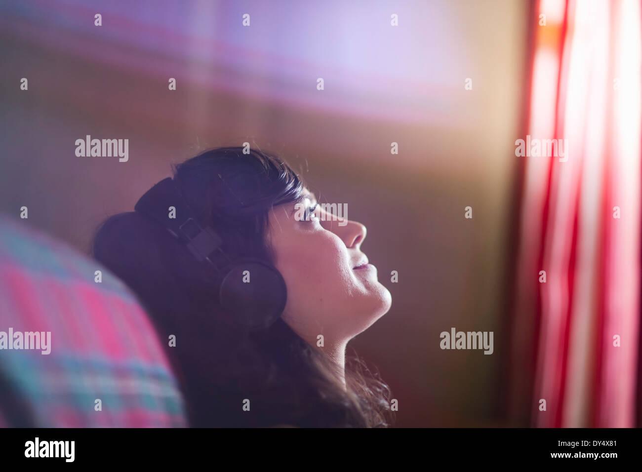 Jeune femme portant des écouteurs, daydreaming Banque D'Images