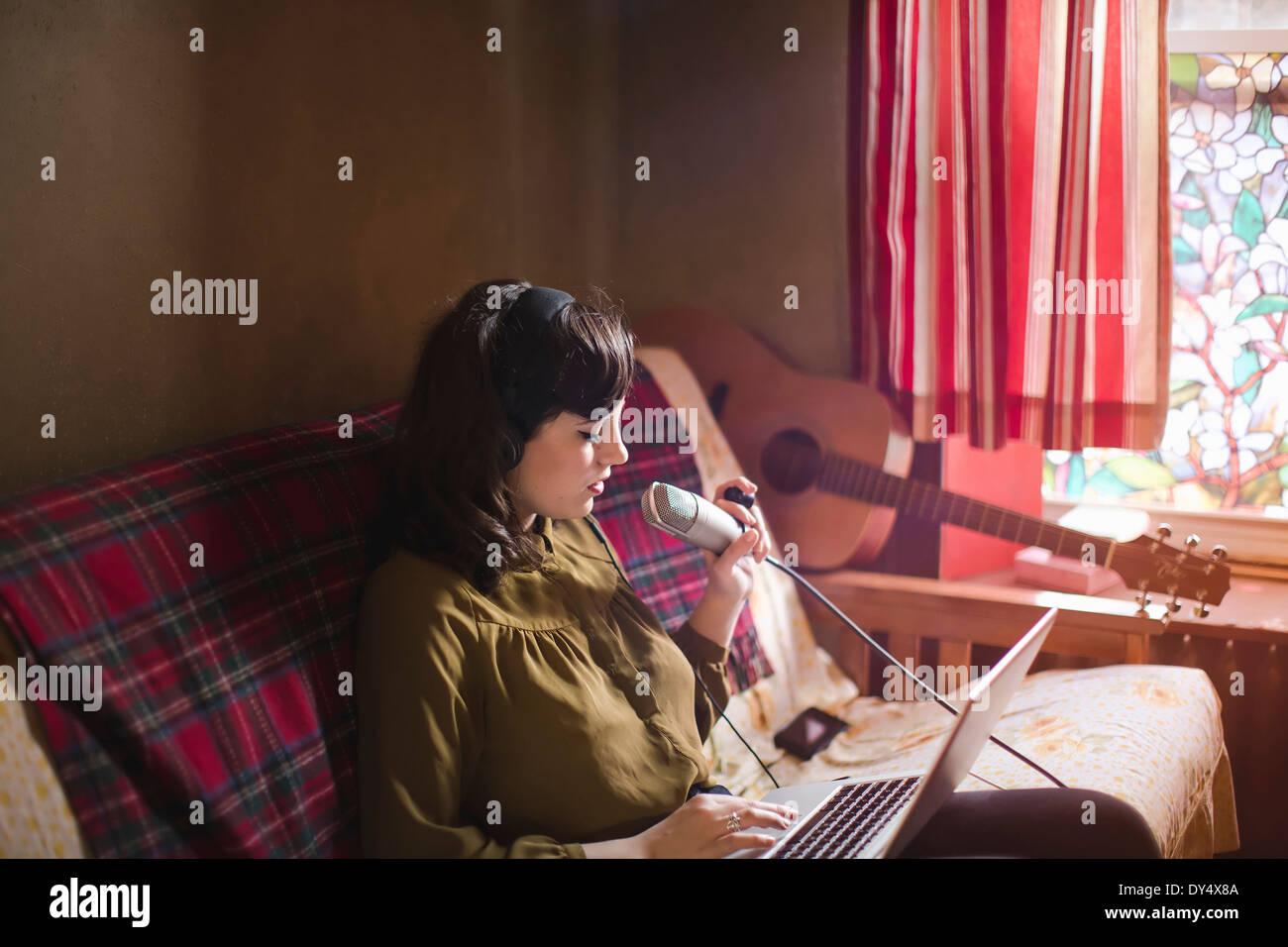 Jeune femme portant des écouteurs et microphone, avec coffre Banque D'Images