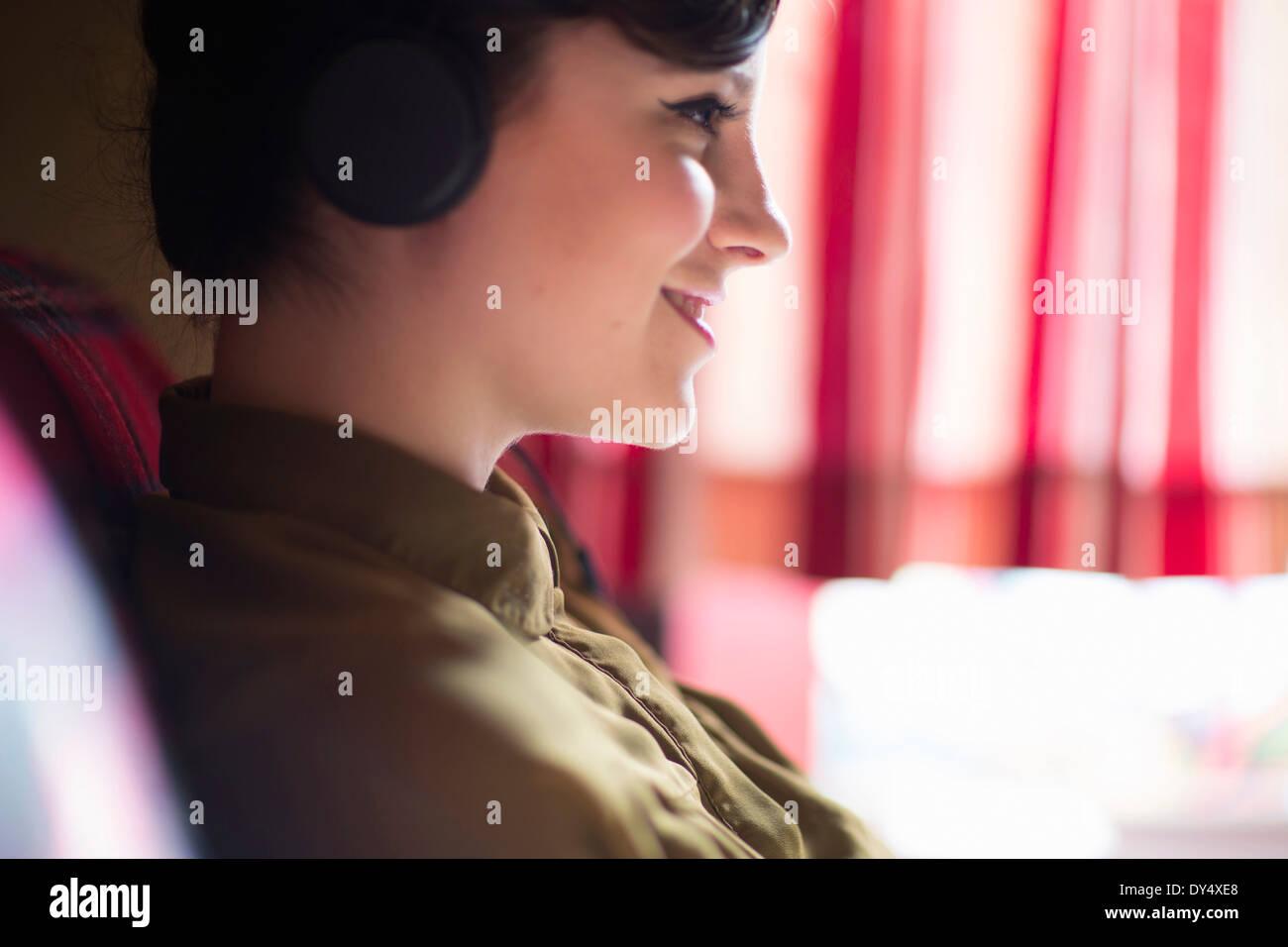 Jeune femme assise sur un canapé, listening to music on headphones Banque D'Images