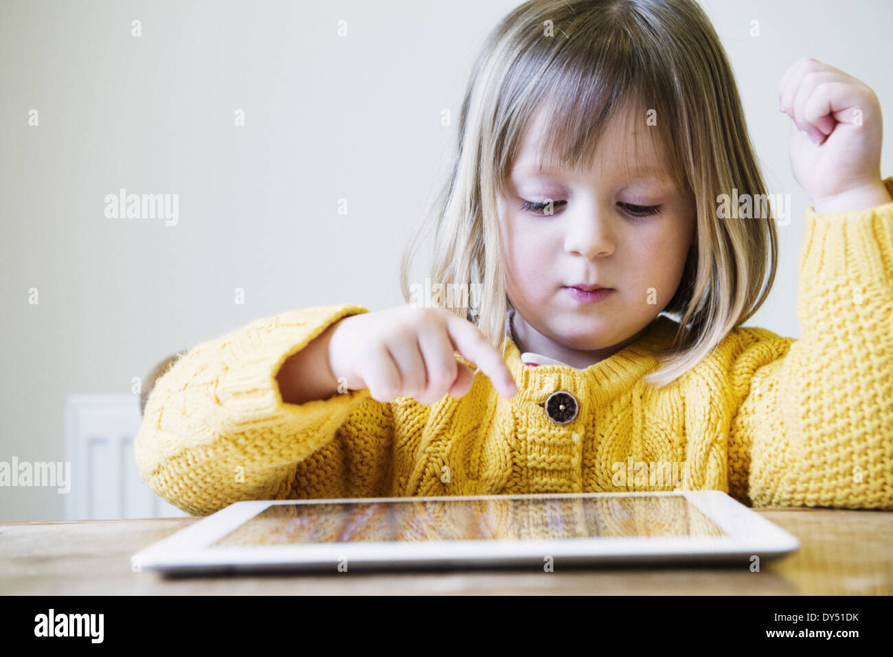 Jeune fille à la table de cuisine using digital tablet Banque D'Images