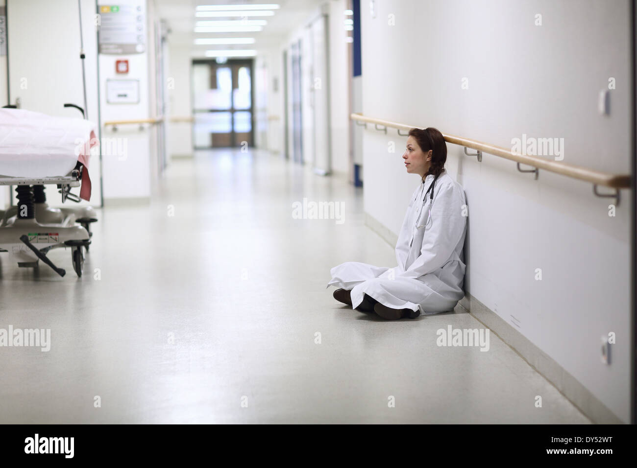 Female doctor sitting cross legged in hospital corridor Banque D'Images