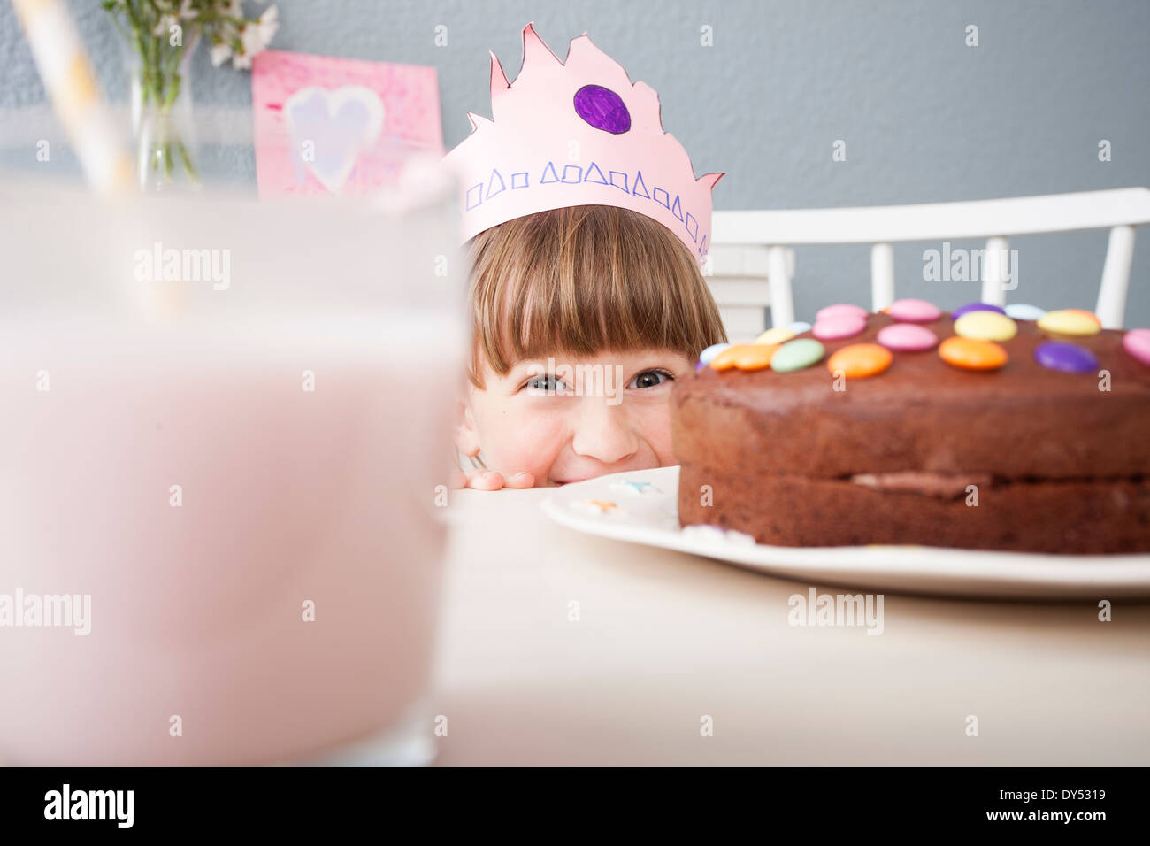 Jeune fille se cacher derrière cake Photo Stock