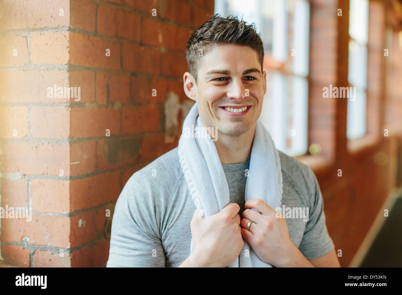 L'homme dans une salle de sport avec une serviette autour du cou Photo Stock