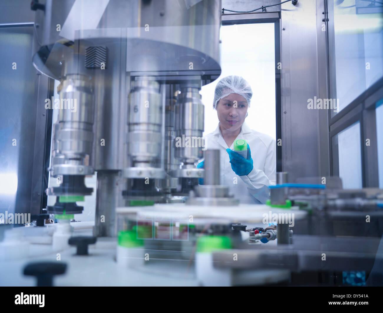 Inspecter les produits des travailleurs sur la ligne de production dans l'usine pharmaceutique Photo Stock