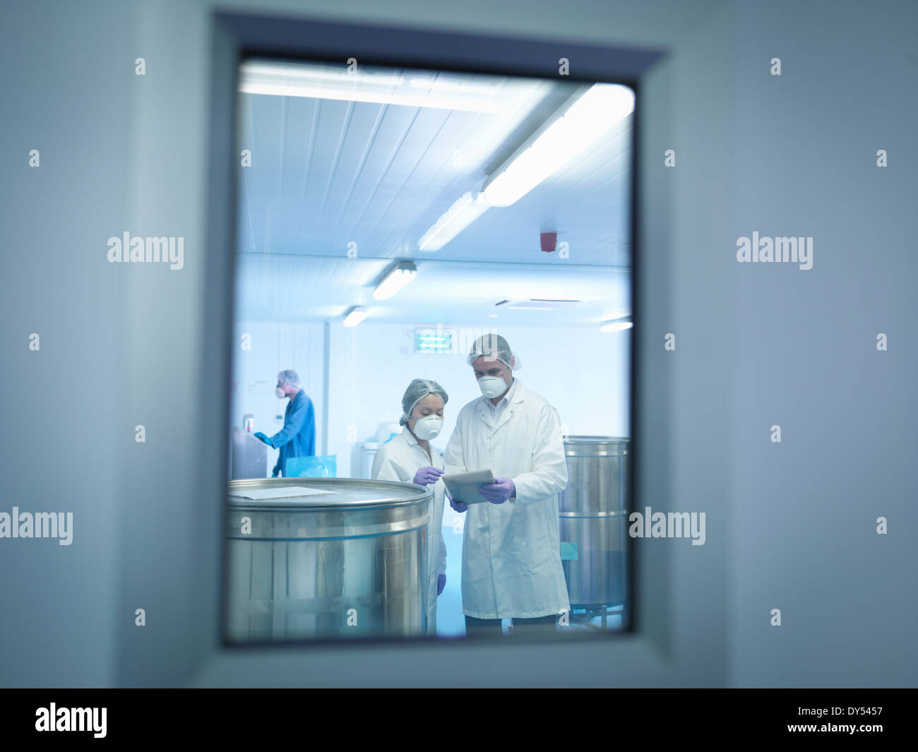 Workers using digital tablet in pharmaceutical factory Photo Stock
