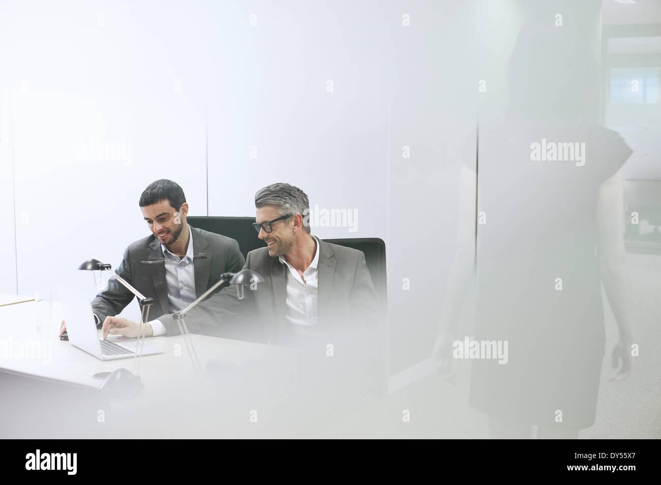 Des collègues masculins using digital tablet in office Banque D'Images