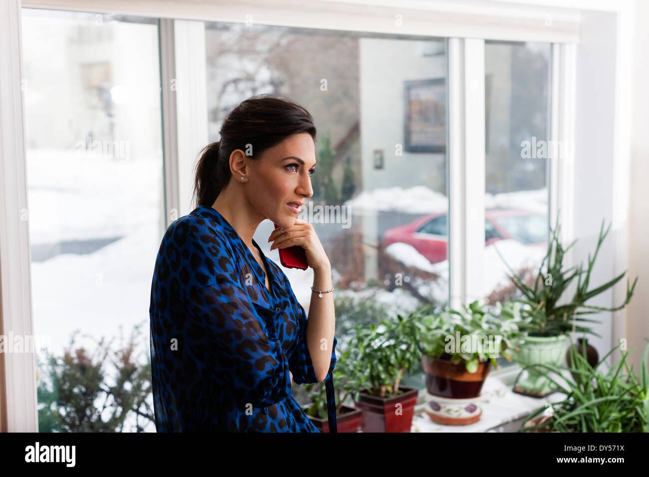 Jeune femme dans la salle de séjour holding cellphone Banque D'Images