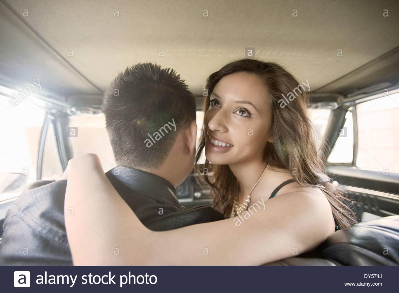 Jeune femme avec bras autour de petit ami sur le siège avant de la voiture Photo Stock