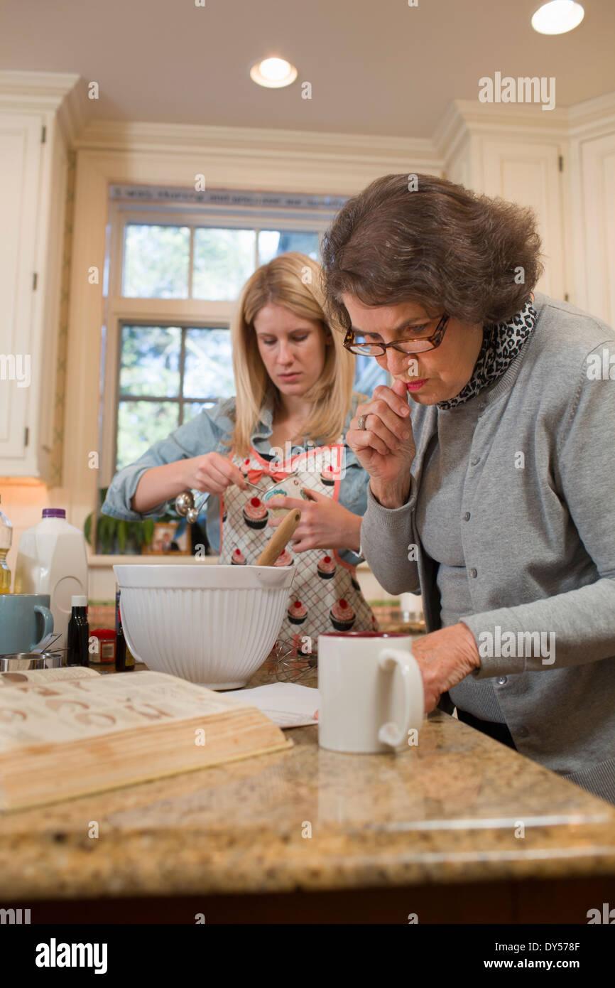 Senior woman et petite-fille de verser la cuisson dans la cuisine Photo Stock