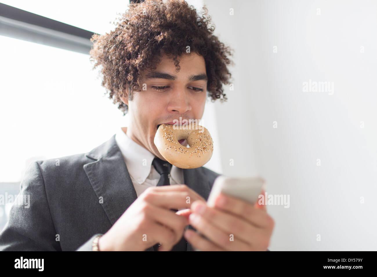 Jeune homme à l'aide de téléphone cellulaire avec bagel en bouche Banque D'Images