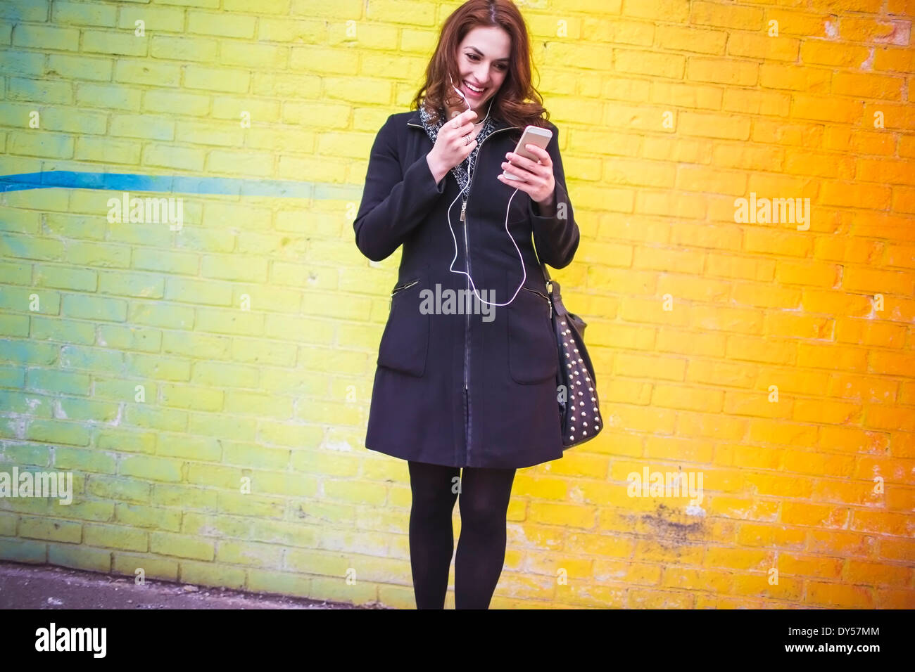Jeune femme choisissant music on city street Photo Stock