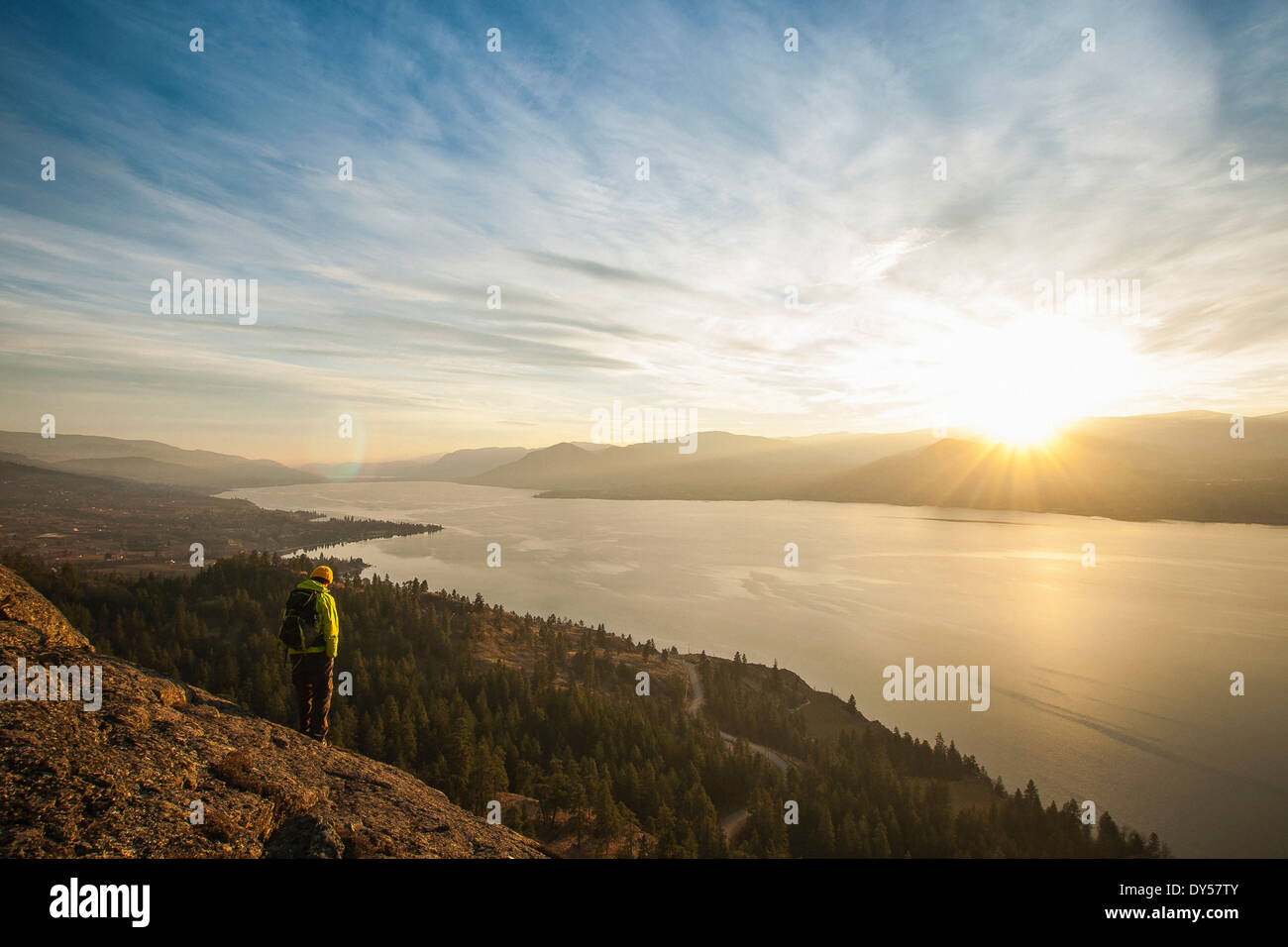 Male hiker regardant le coucher du soleil sur le lac Okanagan, Naramata, British Columbia, Canada Photo Stock