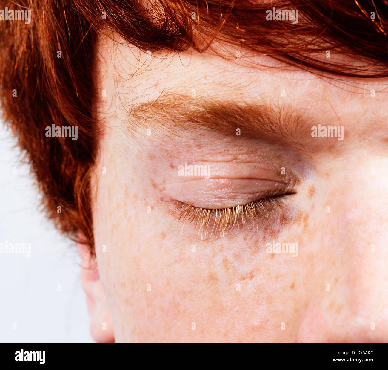 Visage tourné de partiel jeune homme aux cheveux roux et taches de rousseur, les yeux fermés Photo Stock