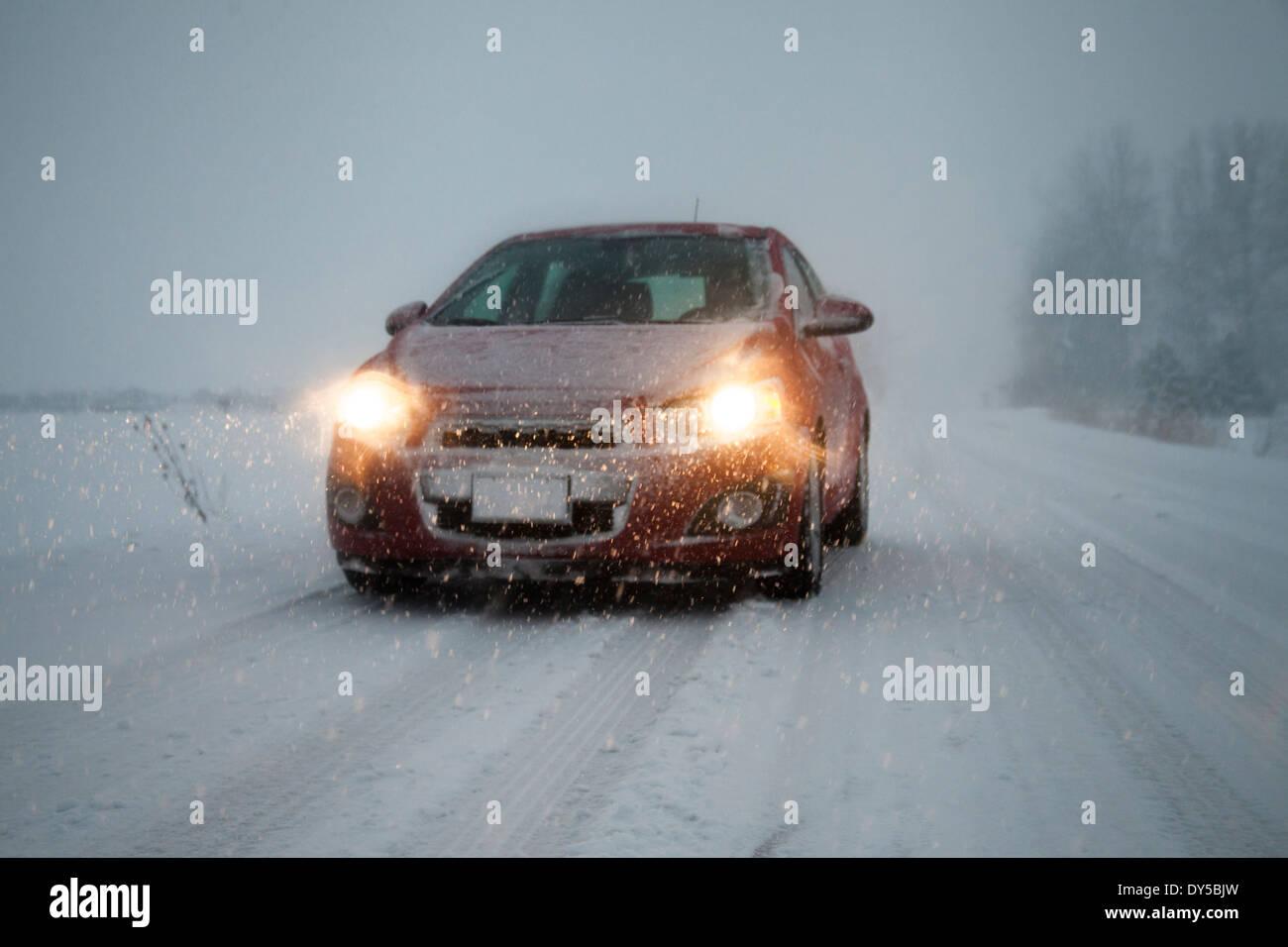Voiture avec phares sur conduite le long de la route couverte de neige brouillard Banque D'Images