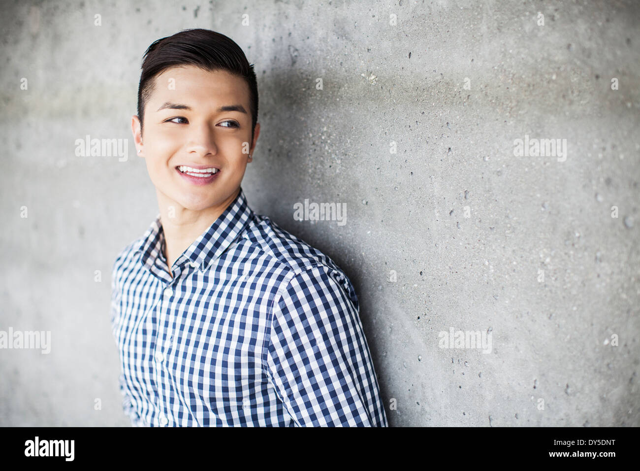 Portrait of young man leaning against wall Photo Stock