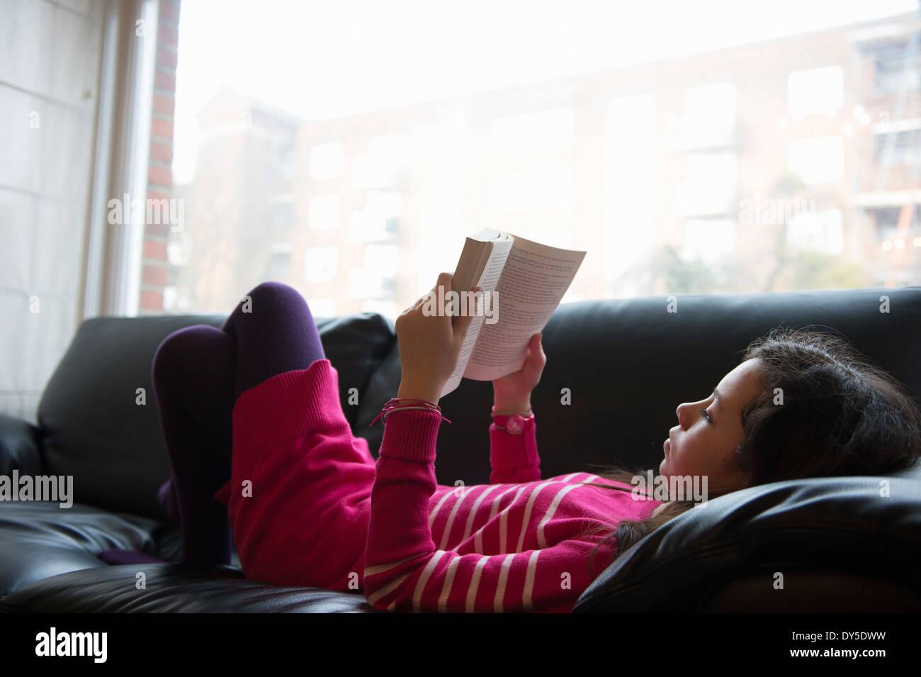 Girl lying on sofa, reading book Photo Stock