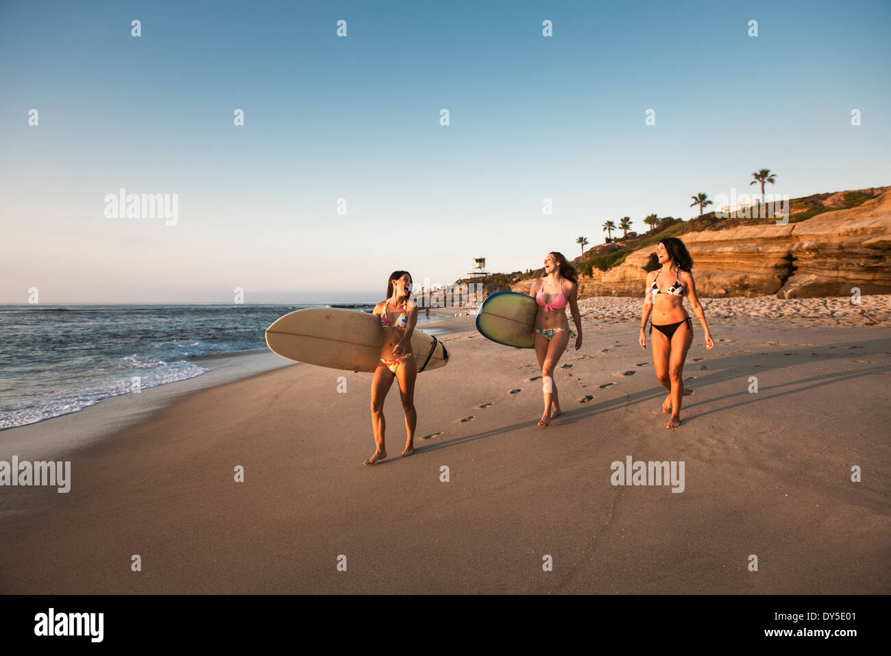 Surfers carrying surf boards, marcher le long beach Photo Stock