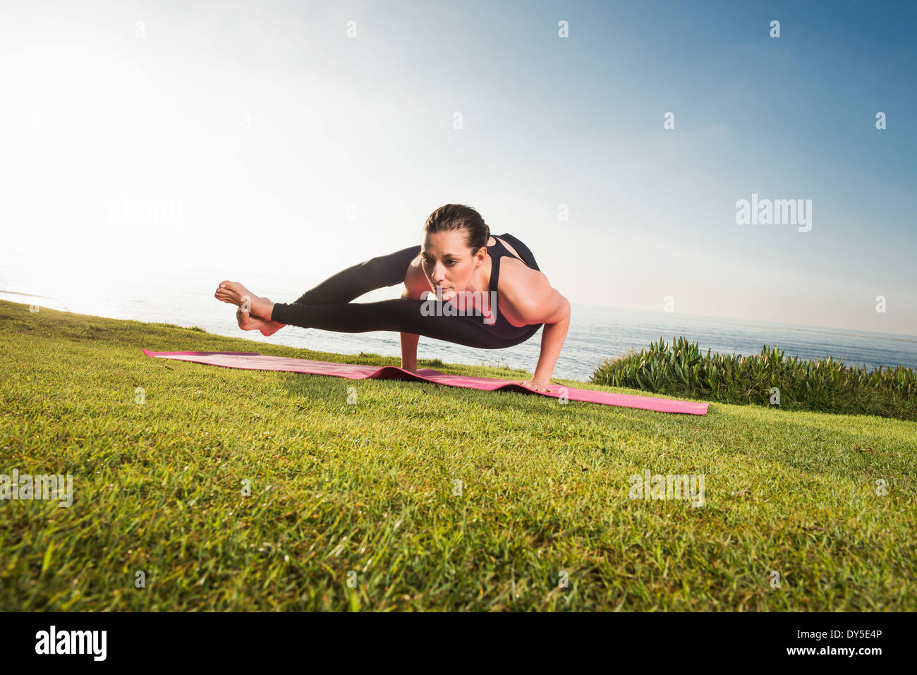 Women on cliff, in yoga position Photo Stock