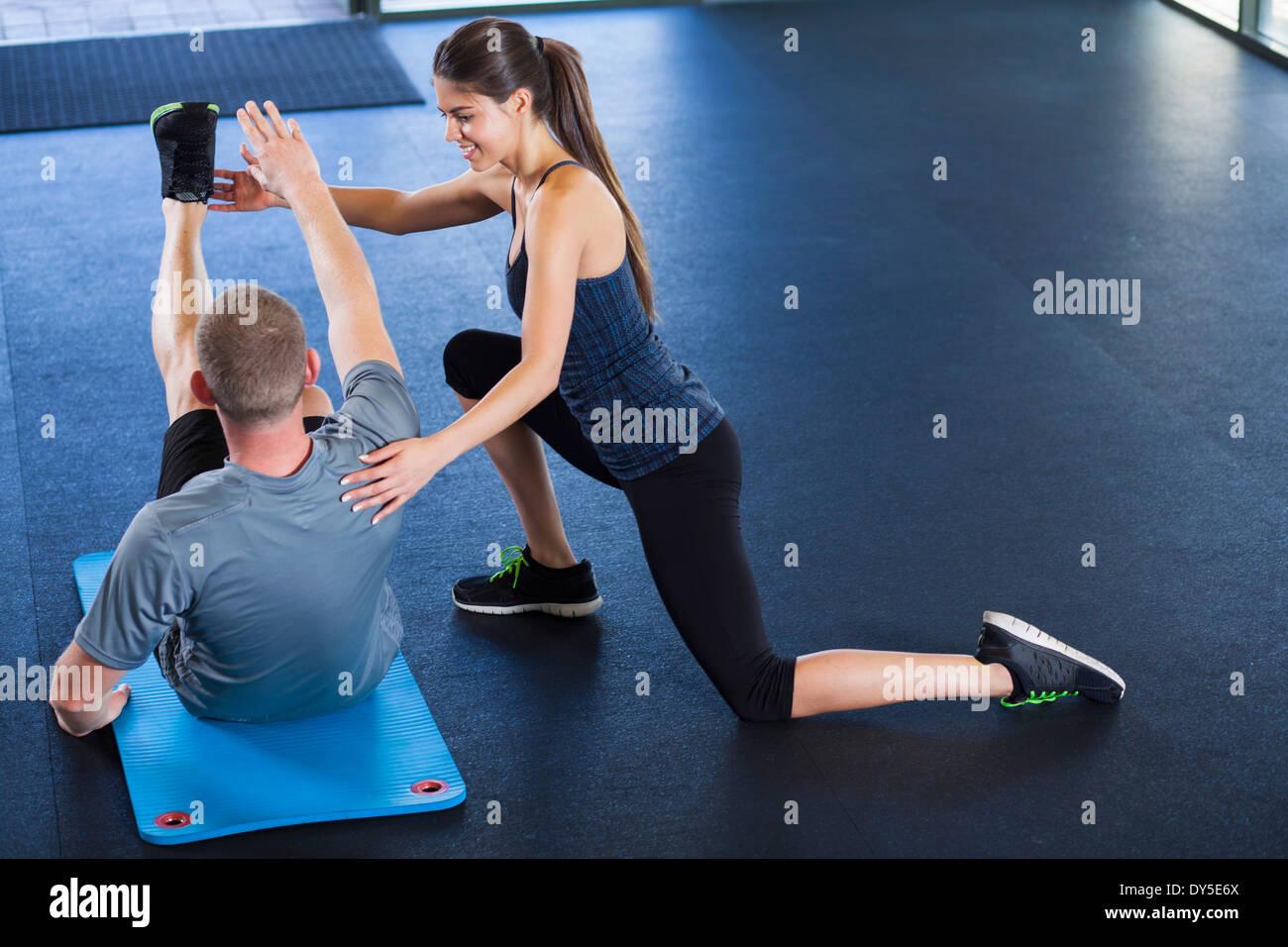 Couple d'aider les uns les autres dans la salle de sport Photo Stock