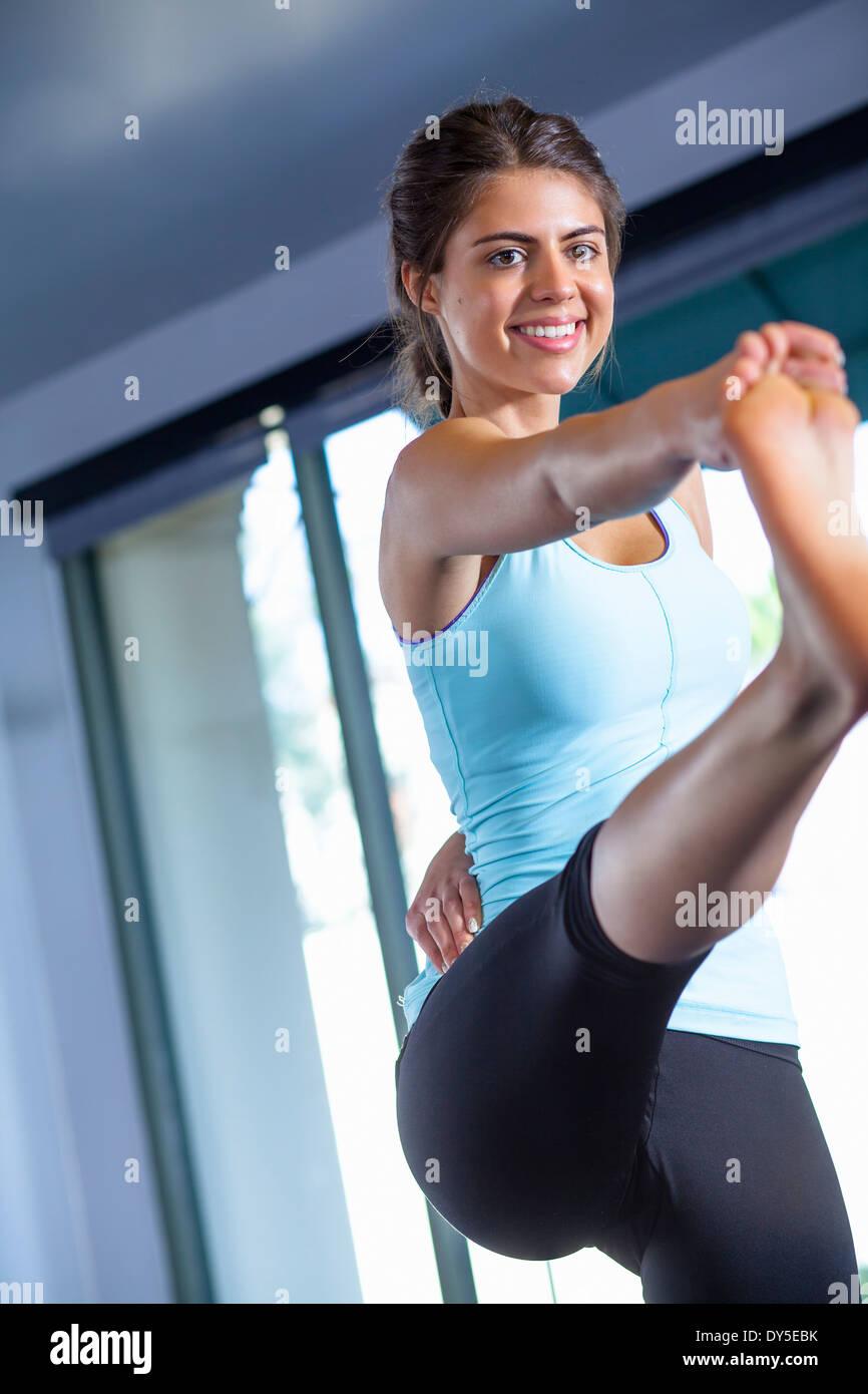 Jeune femme à la jambe tendue poser Photo Stock