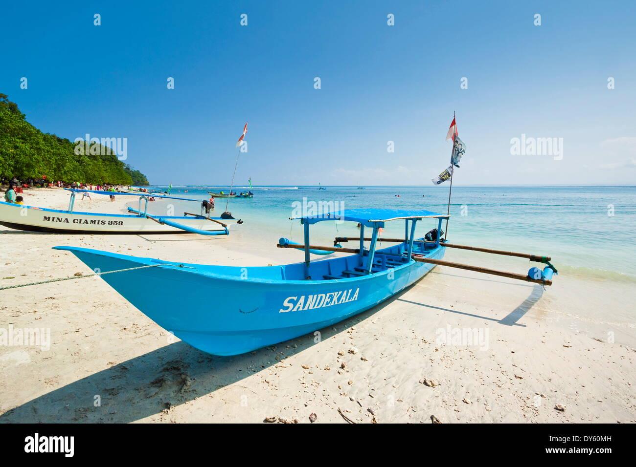 Outrigger bateaux sur magnifique plage de sable blanc dans le parc national sur la côte sud à Pangandaran, West Java, Java, Indonésie Photo Stock
