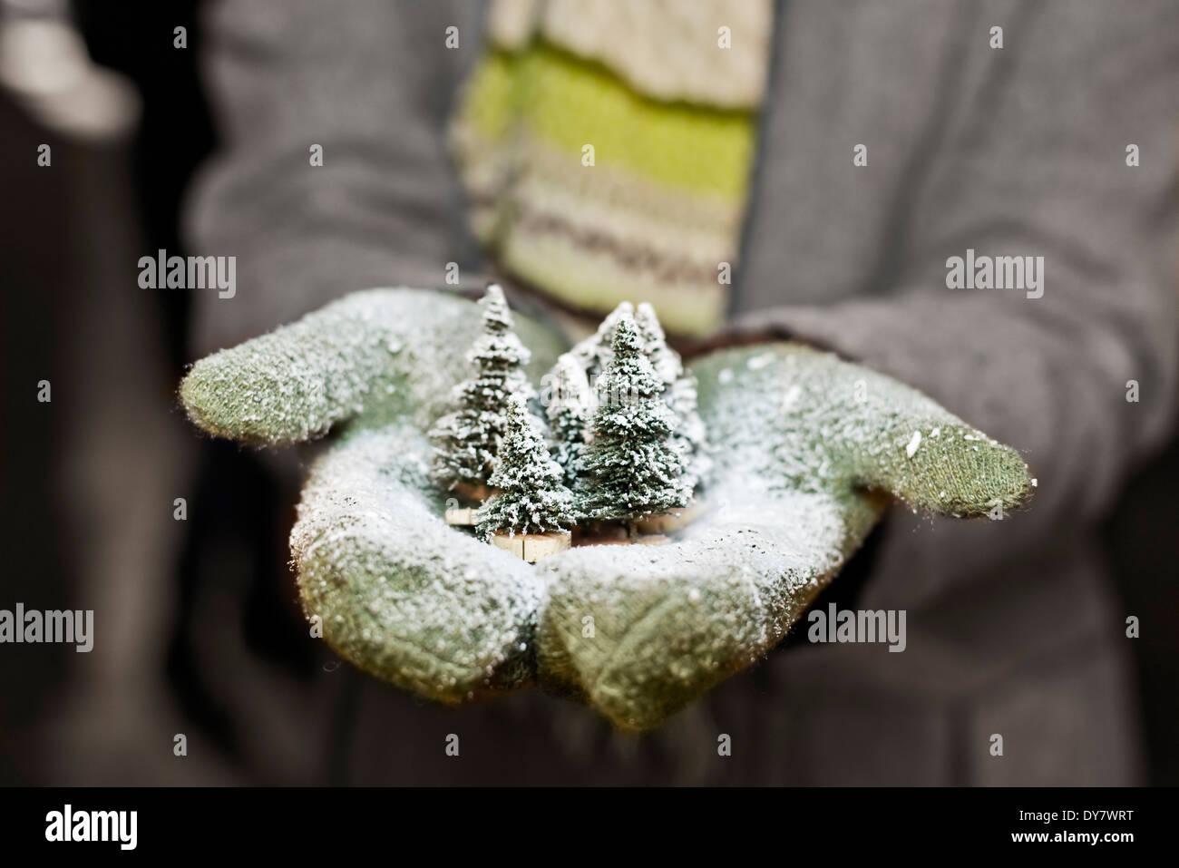 Jeune femme avec des gants holding Christmas decoration, vue partielle Photo Stock