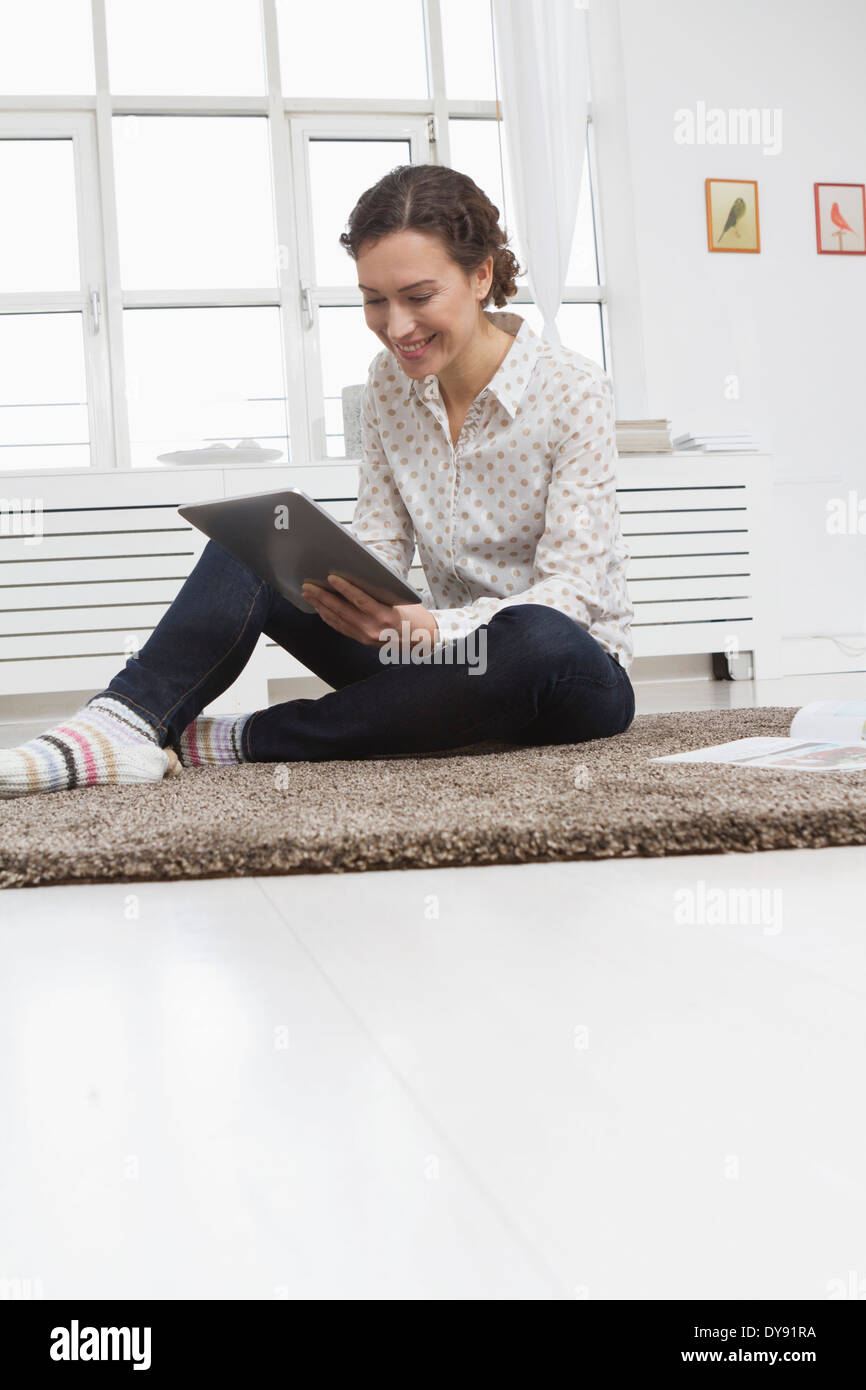 Woman at home using tablet computer Photo Stock