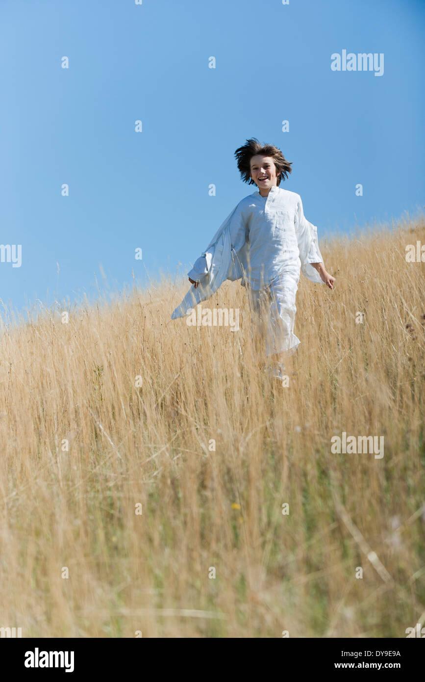 Boy running à travers les hautes herbes Photo Stock