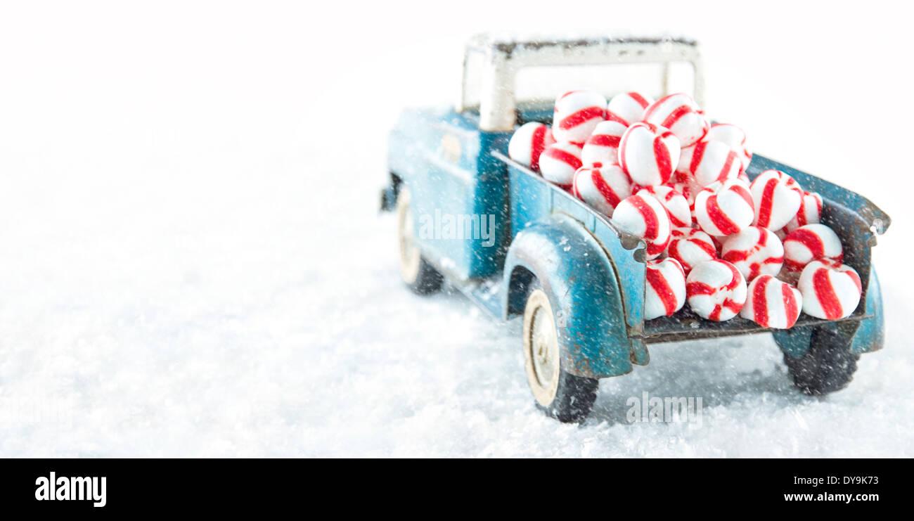 Jouet Ancien bleu camion transportant Peppermint Candy rayé sur blanc snowy bakcground Banque D'Images