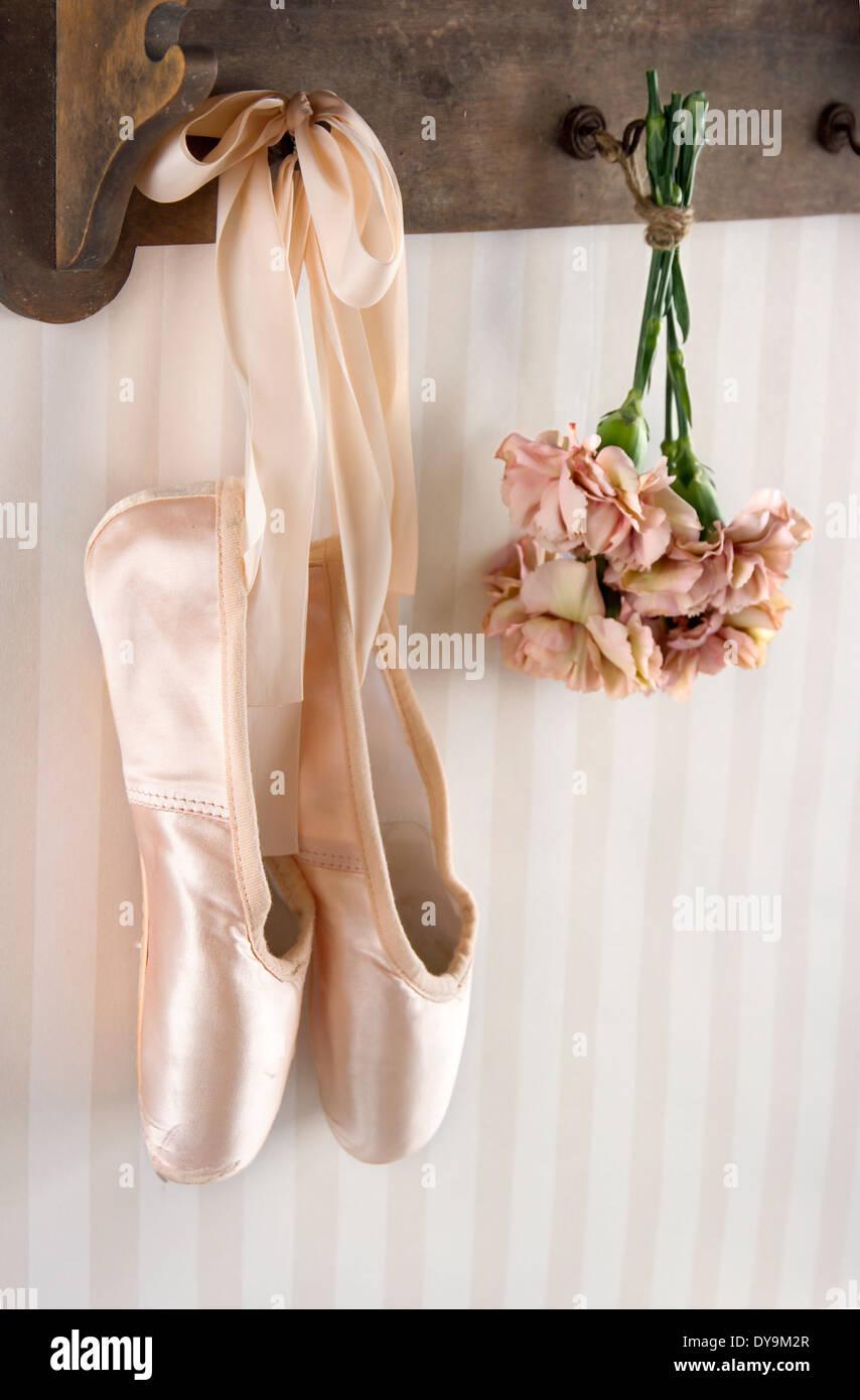 Paire de chaussures de ballet pointe suspendu à un rack sur fond à rayures vintage pour copy space Banque D'Images