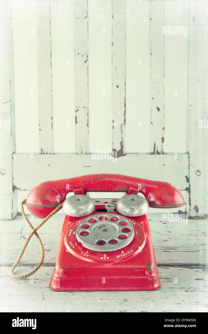 Téléphone jouet rouge sur le bleu clair avec l'édition vintage chaise en bois Banque D'Images