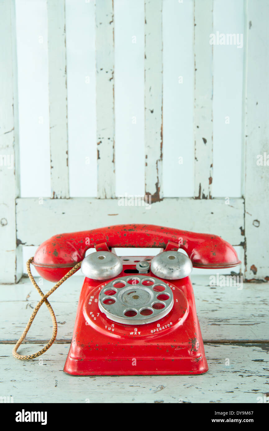 Téléphone jouet rouge sur bleu ciel vintage en bois président Banque D'Images