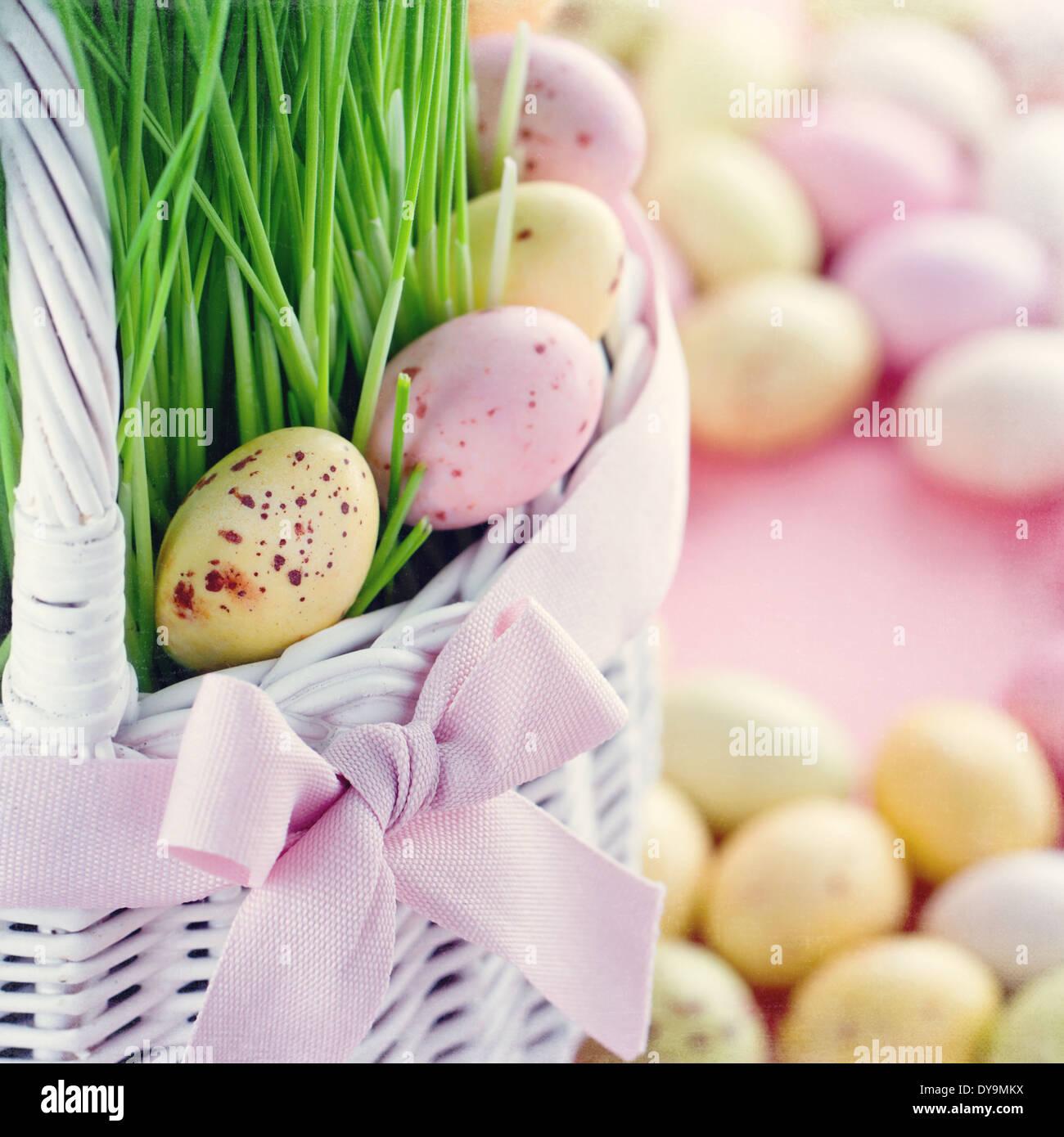 Petit aperçu des oeufs de Pâques dans un panier blanc vert avec l'herbe fraîche sur fond rose de couleur pastel Banque D'Images
