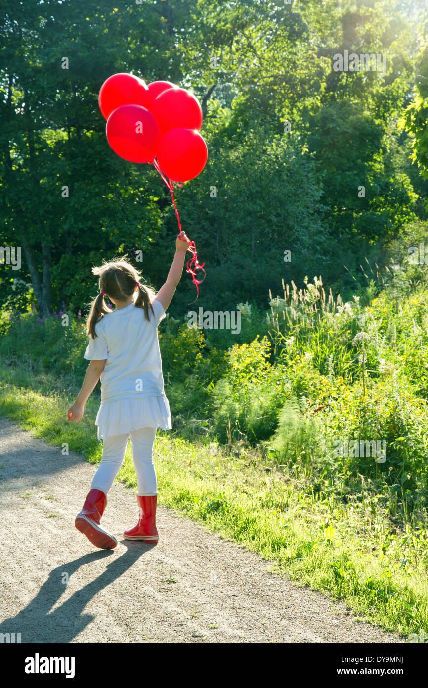 Petite fille avec un bouquet de ballons rouges marchant sur une route de campagne dans un paysage d'été vert avec Banque D'Images