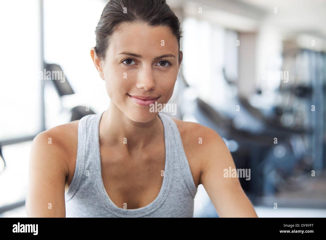 Jeune femme à l'aide de machine d'exercice à la salle de sport Photo Stock