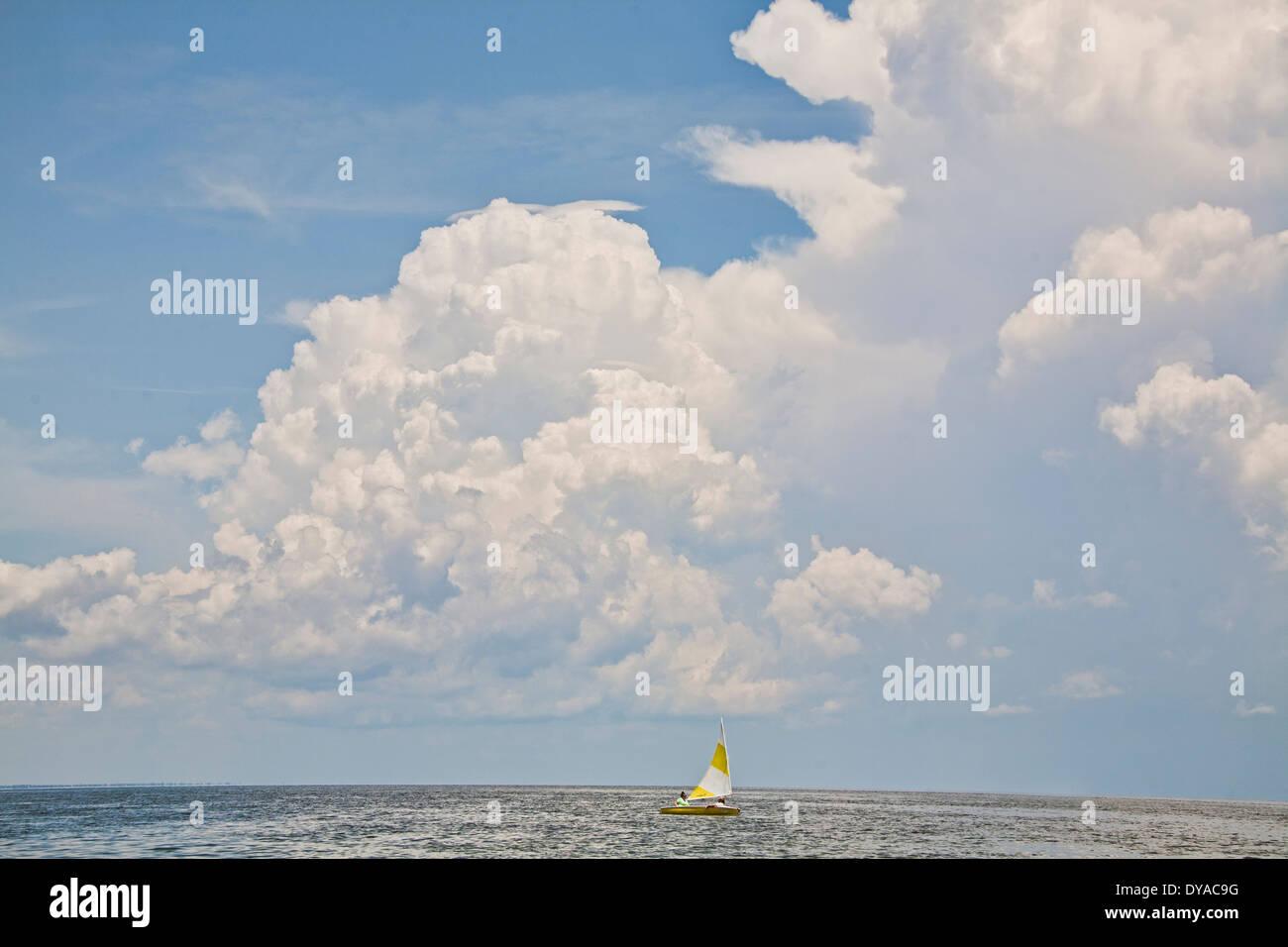 Petit voilier naviguant en Floride sur le golfe du Mexique avec de grands nuages au-dessus de l'horizon Photo Stock