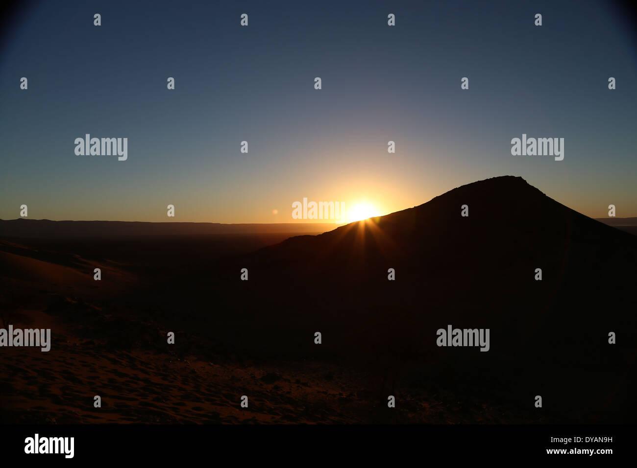Le lever du soleil sur le baron paysage désertique au Maroc au-delà de l'Atlas des chaînes de montagnes, avec des rayons de soleil une dune de sable qui se chevauchent Photo Stock