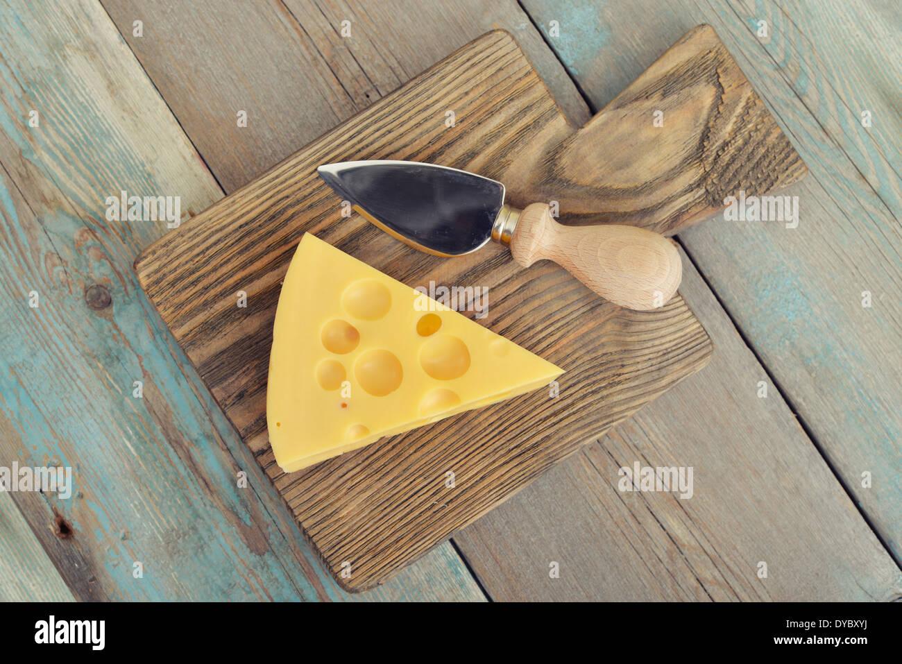 Fromage avec de grands trous et le couteau sur la planche à découper en bois Photo Stock