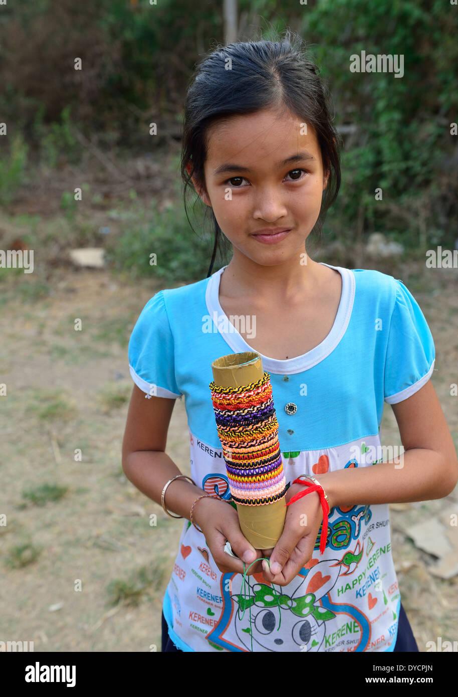 Jeune fille cambodgienne propose ses bracelets et bagues de l'herbe.bijoux pour la vente aux voyageurs des trains de bambou au village de VBL Sra O Photo Stock