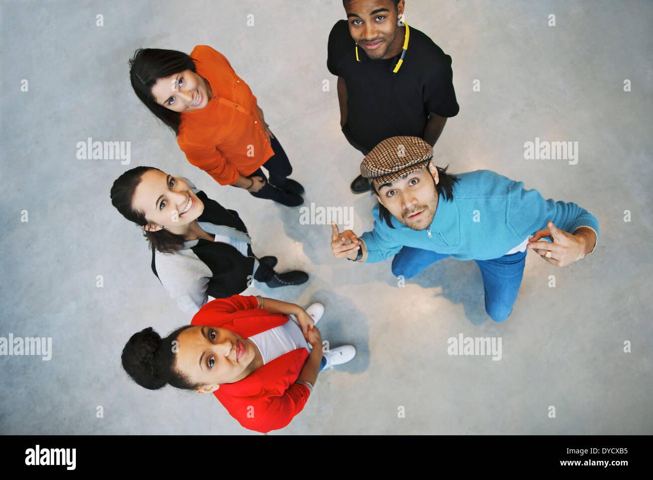 Vue de dessus de jeunes se tenant ensemble à la caméra jusqu'au jeune homme élégant avec des gestes. Équipe ou groupe. Photo Stock